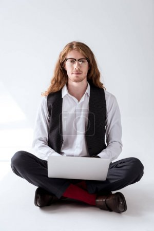 stylish tattooed businessman with ginger hair sitting on floor with laptop