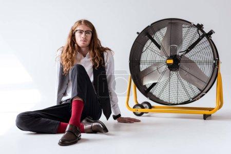 Foto de Empresario con estilo con el cabello rizado sentado en piso cerca gran fan - Imagen libre de derechos