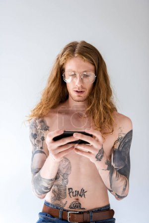 handsome shirtless tattooed man with curly hair looking at smartphone isolated on white