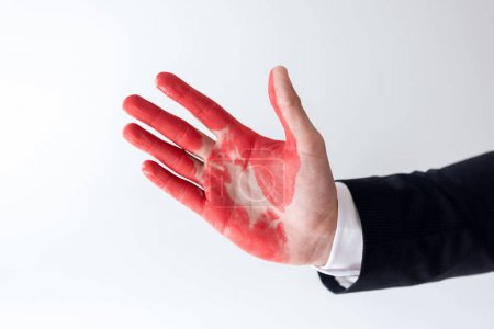 cropped image of businessman showing hand in red paint isolated on white