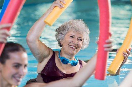 Photo pour Femme âgée souriante faisant de l'aquagym avec des nouilles de natation. Heureuse femme mature et en bonne santé qui prend des cours de fitness en aquagym. Vieille femme en bonne santé tenant des nouilles de natation à la main faisant de l'aquagym avec jeune entraîneur - image libre de droit