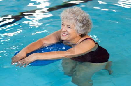 Photo for Happy senior woman with kickboard in a swimming pool. Old woman swimming in water with the help of a kickboard. Smiling old woman swimming with inflatable board in swimming pool. - Royalty Free Image