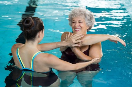 Senior woman stretching in pool
