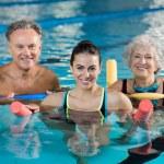 Happy mature man and old woman doing aqua aerobics...