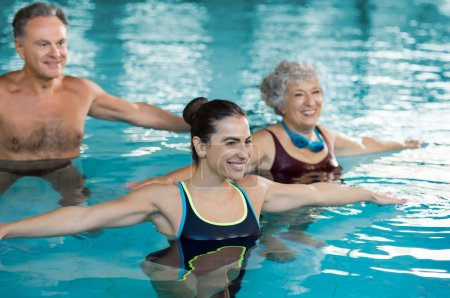 Photo for Smiling fitness class doing aqua aerobics in swimming pool. Smiling young woman with senior couple stretching arms in swimming pool while doing aqua aerobics. Fit mature man and old woman exercising in swimming pool with young woman. - Royalty Free Image