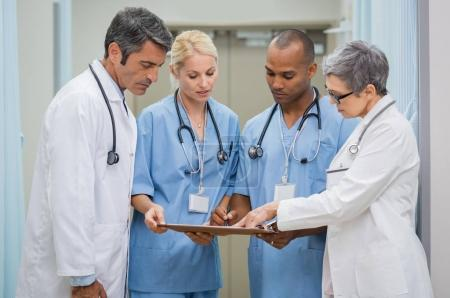 Photo for Group of senior doctors and young nurses examining medical report of patient. Team of doctors working together on patients file at hospital. Medical staff analyzing and working at clinic. - Royalty Free Image