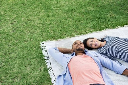 Photo for Young multiethnic couple lying on blanket on grass. Latin woman with her african boyfriend relaxing on picnic blanket outdoor. Mature happy couple in love lying on grass with copy space. - Royalty Free Image