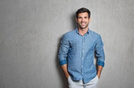 Foto de Retrato de un guapo joven sonriendo contra el fondo gris con espacio de copia. Chico sonriente con las manos en el bolsillo de la camisa azul de pie y apoyado en la pared. Hombre hispano exitoso mirando a cámara. - Imagen libre de derechos