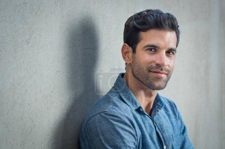 Photo for Handsome young man posing on grey background. Portrait of satisfied businessman against grey wall. Close up face of fashionable latin man on grey background. - Royalty Free Image