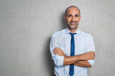 Photo pour Heureux homme d'affaires mature en chemise bleue et cravate, regardant la caméra. Portrait de souriant et satisfait l'homme d'affaires hispanique avec bras croisés isolé sur fond gris avec espace de copie. Homme senior prospère, debout sur le mur gris. - image libre de droit