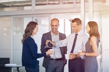 Photo pour Homme d'affaires versant du café pour des collègues dans une salle de réunion. Les hommes d'affaires et les femmes d'affaires prennent une pause café après la conférence. Bonne équipe d'affaires formelle boire du café et se détendre au travail . - image libre de droit
