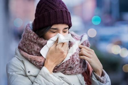 Photo pour Jolie jeune femme qui se mouche avec un mouchoir en plein air en hiver. Une jeune femme tombe malade de la grippe un jour d'hiver. Femme avec un rhume . - image libre de droit