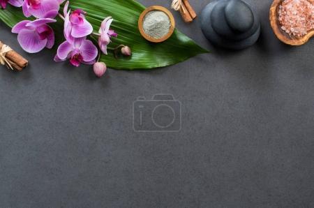 Photo pour Vue de dessus du spa avec des pierres chaudes, des orchidées et du sel rose. Vue grand angle des orchidées avec feuille verte sur tableau noir avec pierre chaude empilée pour le traitement de massage. Spa luxueux et élégant avec espace de copie . - image libre de droit