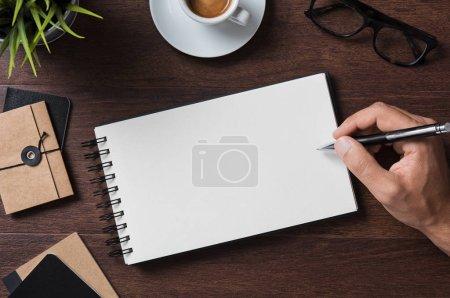 Photo pour Vue du dessus de l'homme d'affaires écrivant sur carnet vierge. Vue grand angle de l'homme écriture à la main sur bloc-notes vide avec lunettes, tasse à café et dossier sur table en bois. Gros plan d'un homme d'affaires prenant des notes - image libre de droit