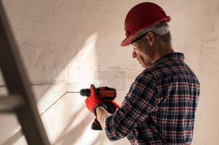 Man drilling hole in wall