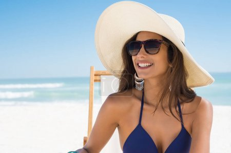 Happy woman with straw hat at beach
