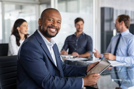 Photo pour Mature black businessman with colleagues sitting in a modern board room. Proud smiling business man sitting during a meeting and looking at camera. Portrait of happy successful executive with team working in background. - image libre de droit