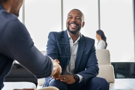 Photo pour Two happy mature business men shaking hands in modern office. Successful african american businessman in formal clothing closing deal with handshake. Multiethnic businessmen shaking hands during a meeting. - image libre de droit