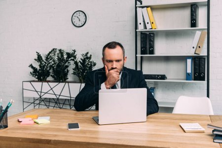 portrait of concentrated businessman working on laptop at workplace in office