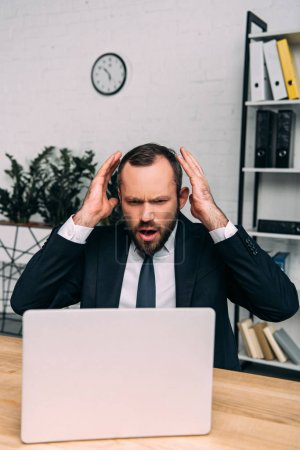Photo for Portrait of stressed businessman at workplace with laptop in office - Royalty Free Image
