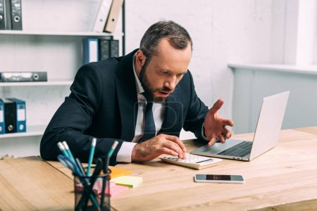 shocked and stressed businessman with calculator at workplace with laptop in office