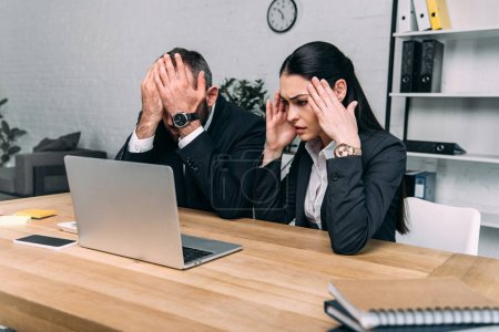 partial view of overworked business people at workplace with laptop in office