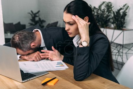 overworked businessman and tired business colleague at workplace with documents and laptop in office