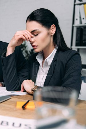 selective focus of tired businesswoman in suit at workplace in office