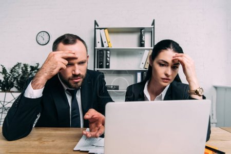 portrait of tired business people looking at laptop screen at workplace in office