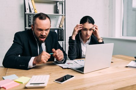 Photo for Stressed and overworked business people at workplace with documents and laptop in office - Royalty Free Image