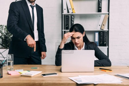 cropped shot of stressed businesswoman and colleague at workplace with laptop in office