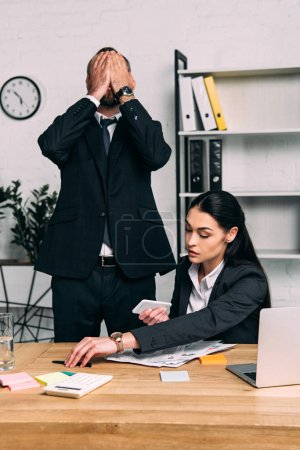 obscured view of overworked businessman and focused businesswoman at workplace with laptop in office
