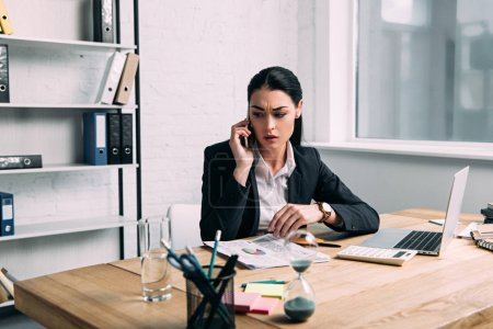 businesswoman in suit talking on smartphone at workplace with calculator and papers in office