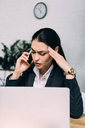stressed businesswoman in suit talking on smartphone at workplace with laptop in office