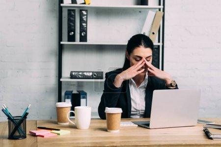 Foto de Retrato de mujer de negocios con exceso de trabajo en traje en el lugar de trabajo con ordenador portátil y café para ir en la oficina - Imagen libre de derechos