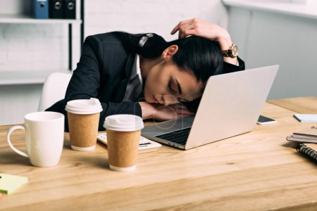 overworked businesswoman sleeping at workplace with laptop and coffee to go in office