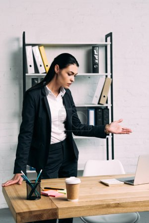 portrait of overworked businesswoman standing at workplace with laptop in office