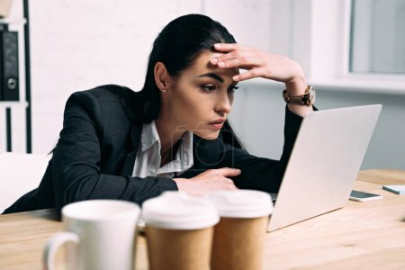 side view of tired businesswoman in suit working on laptop at workplace in office