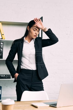 Photo for Portrait of overworked businesswoman standing at workplace with laptop in office - Royalty Free Image