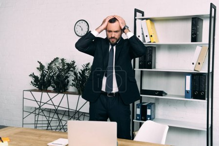 portrait of stressed businessman in suit standing at workplace in office