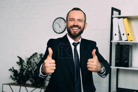 Foto de Retrato de sonriente hombre de negocios en traje mostrando los pulgares para arriba en oficina - Imagen libre de derechos