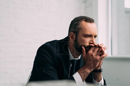 side view of tired and pensive businessman in suit looking away in office