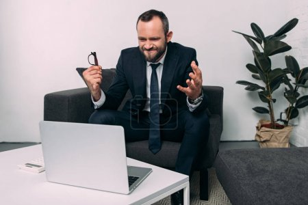 portrait of overworked businessman with eyeglasses looking at laptop on coffee table in office