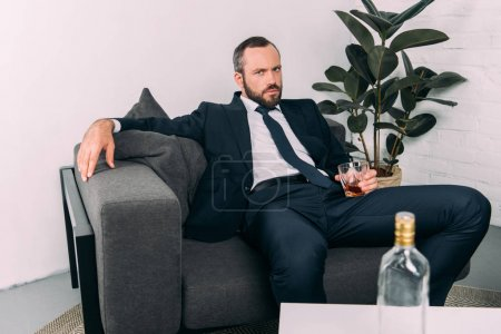 Photo for Portrait of businessman in suit with glass of alcohol resting on sofa at coffee table in office - Royalty Free Image