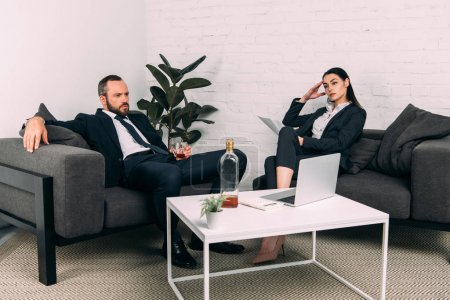 tired business colleagues at coffee table with laptop and alcohol in office