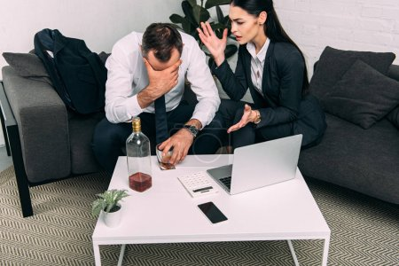 Photo for Partial view of stressed business colleagues at coffee table with laptop and alcohol in office - Royalty Free Image