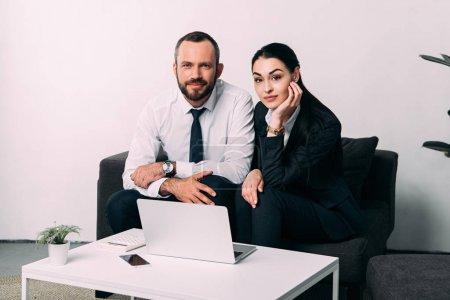 Photo pour Portrait de collègues de travail, regardant la caméra tout en restant assis à table de café avec ordinateur portable au bureau - image libre de droit