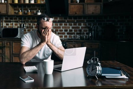 overworked freelancer remote working at table with laptop in kitchen at home