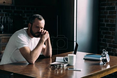 depressed young man sitting on kitchen with laptop and looking away