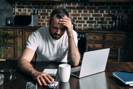 depressed young man sitting on kitchen with laptop and crumpled photo of ex-girlfriend